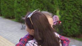 A mulher com uma inabilidade em uma cadeira de rodas abraça o adolescente Mo lento vídeos de arquivo