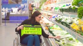 A mulher com uma inabilidade em uma cadeira de rodas escolhe os bens na compra no supermercado Fim acima filme