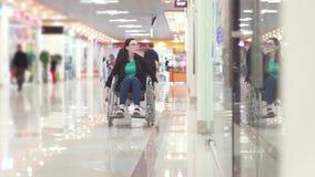 A mulher com uma inabilidade em uma cadeira de rodas monta ao shopping e olha as janelas vídeos de arquivo