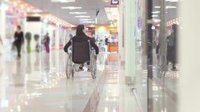 Mulher com uma inabilidade em uma cadeira de rodas que vai à alameda video estoque