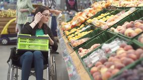 A mulher com uma inabilidade em uma compra da cadeira de rodas no supermercado escolhe frutos e põe-nos em um pacote filme