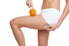 Mulher com uma laranja que mostra uma pele perfeita Imagens de Stock Royalty Free