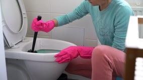 A mulher com uma luva de borracha limpa uma bacia de toalete filme