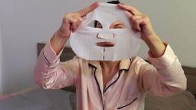 Mulher com uma máscara cosmética em suas mãos video estoque