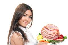 Mulher com uma placa com presunto cortado foto de stock