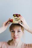 Mulher com uma placa do bolo em sua cabeça Fotografia de Stock