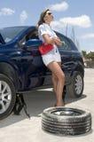 Mulher com uma roda quebrada de seu carro Imagem de Stock Royalty Free