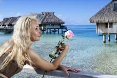 A mulher com uma rosa em uma mão olha o mar e as casas sobre a água tahiti Imagem de Stock