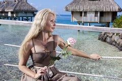 A mulher com uma rosa em uma mão olha o mar e as casas sobre a água tahiti Fotografia de Stock Royalty Free