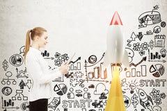 Mulher com uma tabuleta, foguete startup fotografia de stock