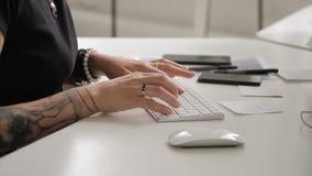 A mulher com uma tatuagem em sua mão imprime no teclado e o rato trabalha vídeos de arquivo