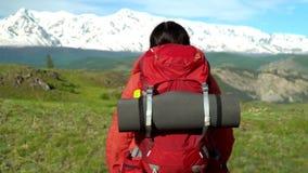 A mulher com uma trouxa vermelha vai acima do verde um sofrimento Vista de montanhas da neve Manhã Sun A mulher nas mãos tem vara video estoque