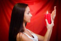 Mulher com vela de encontro ao fundo vermelho Fotos de Stock Royalty Free