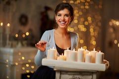 Mulher com velas, chaminé, luzes de Natal fotografia de stock royalty free