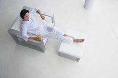 Mulher com vidro de Juice In Armchair alaranjado Imagem de Stock Royalty Free