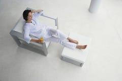 Mulher com vidro de Juice In Armchair alaranjado Fotos de Stock Royalty Free