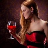Mulher com vidro de vinho vermelho da terra arrendada do cabelo Foto de Stock