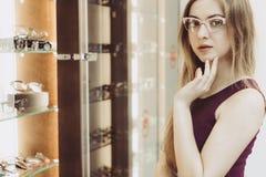 Mulher com vidros no salão de beleza ótico foto de stock