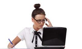 A mulher com vidros senta-se em uma tabela e em um trabalho Imagens de Stock