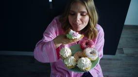 A mulher come demais o queque doce na mesa de cozinha Mulher com fome que come a sobremesa vídeos de arquivo