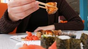 A mulher come o sushi Rolls com hashis em um restaurante japonês vídeos de arquivo