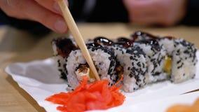 A mulher come o sushi Rolls com hashis em um restaurante japonês filme
