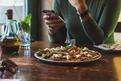 A mulher come a pizza imagem de stock royalty free
