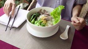 A mulher come a sopa de macarronete tradicional da carne de Vietname Pho BO com hashis vídeos de arquivo