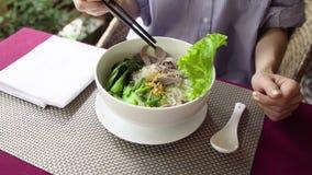 A mulher come a sopa de macarronete tradicional da carne de Vietname Pho BO com hashis Foto de Stock
