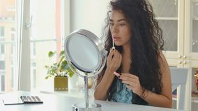 A mulher compõe na frente do espelho video estoque