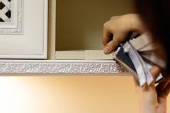A mulher compara e mede usar o teste padrão da textura e a paleta de cores coloridos - amostras de folha a escolher de fotografia de stock
