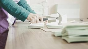 A mulher complementa as páginas do folheto com um martelo na indústria do polígrafo, trabalho manual video estoque