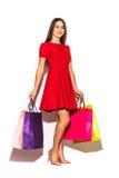 Mulher completa da altura com os sacos shoping da cor nas mãos no fundo branco imagem de stock