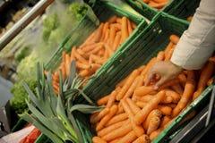 A mulher compra o fruto e o alimento no supermercado Imagens de Stock