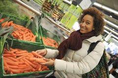 A mulher compra o fruto e o alimento no supermercado Imagens de Stock Royalty Free