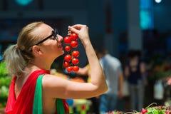 A mulher compra tomates Fotografia de Stock Royalty Free