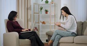 A mulher comprimida tem uma sessão de terapia no psicólogo eles que sentam-se no sofá, paciente que fala no telefone então vídeos de arquivo