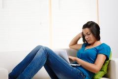 Mulher concentrada ao usar um portátil Imagens de Stock Royalty Free