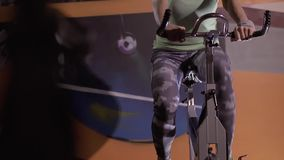 Mulher concentrada da aptidão nos pedais de giro do gym da bicicleta de exercício filme