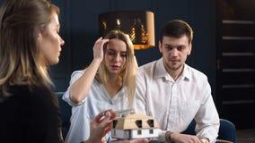 Mulher concentrada e homem que escolhem o modelo da casa video estoque
