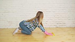 Mulher concentrada que lustra o assoalho de madeira Moça nas luvas protetoras que lavam o apartamento, conceito spring cleaning filme