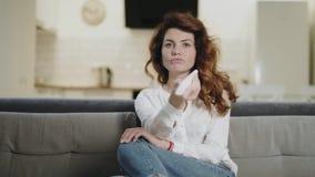 Mulher concentrada que procura o programa da tevê na cozinha moderna video estoque