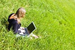 Mulher conectada na grama Fotos de Stock