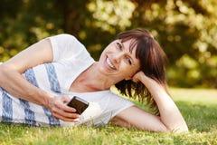 Mulher confortável alegre que encontra-se na grama com telefone esperto foto de stock