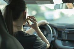Mulher confundida que fala em seu telefone ao conduzir imagem de stock