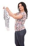 Mulher confundida que guarda a camisa nova Foto de Stock
