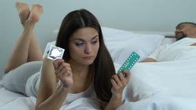 Mulher confundida que guarda o preservativo e comprimidos orais, escolha da contracepção, cuidados médicos video estoque