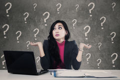 Mulher confusa com pontos de interrogação no escritório Fotografia de Stock Royalty Free