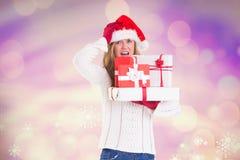 Mulher confusa no chapéu de Santa que guarda sua pilha de presentes Foto de Stock