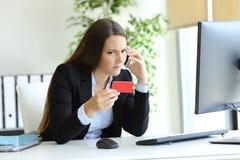 Mulher confusa que chama o banco sobre o cartão de crédito errado fotos de stock